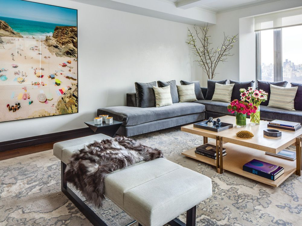 Holly Hunt cotton velvet on the custom sectional juxtaposed with Jiun Ho's bleached oak-and-steel coffee table. The grouping sits on a custom silk-wool rug from Holland & Sherry near a Christian Chaize photo of Praia Piquinia in Portugal.