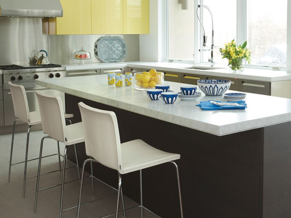 Stainless steel, ebony wood, and white Corian countertops offset the kitchen's lacquered yellow cabinetry.