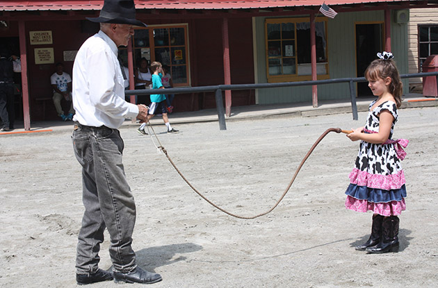 cowgirl holds bull whip