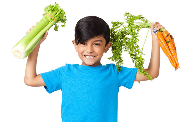 happy boy holding vegetables