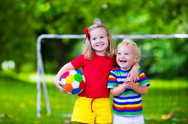young girl and boy on soccer field with soccer ball