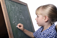 child writing on chalboard; young girl doing writing math problems on a chalkboard