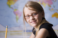 young girl in classroom sitting at desk, map in background