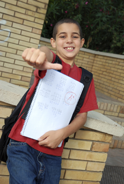 young boy at school giving a thumbs up