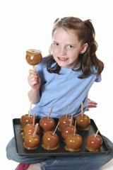 caramel apples; girl making caramel apples for halloween