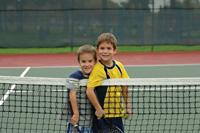 free tennis lessons in Manhattan; two boys playing tennis
