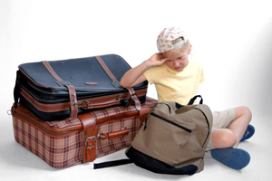 child packing for summer camp; child packing a suitcase