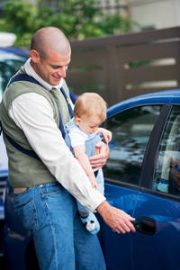 new dad with baby opening car door; father and child getting in a car; new father's survival guide