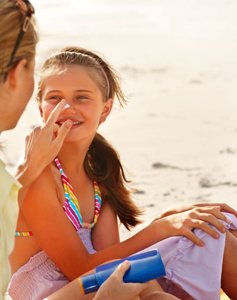 mom putting sunblock on daughter; outdoor summer safety for kids; sunscreen