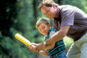 father and son playing baseball; father teaching son to play baseball