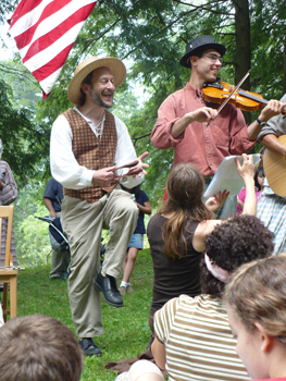 Musicians play the spoons, fiddle, and guitar while guests dance.