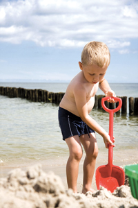 little boy digging in the sand at the beach; young boy playing at the beach