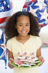 fourth of july; independence day; july 4; young girl holding plate of 4th of July cookies; little girl holding cookies