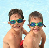boys in goggles; young boys, brothers swimming at the pool
