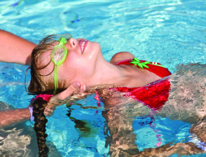young girl learning to swim; child swimming