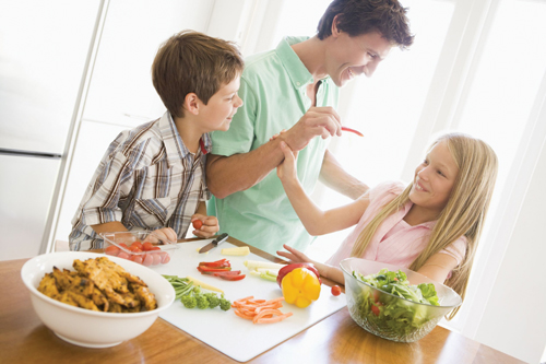parents and kids in the kitchen; children eating vegetables, veggies; dad feeding daughter