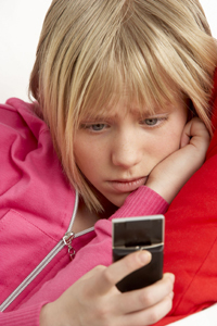 child reading a text message; young girl receives distressing text; cyber bullying