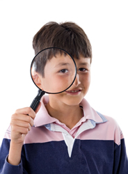child holding a magnifying glass; young boy playing detective
