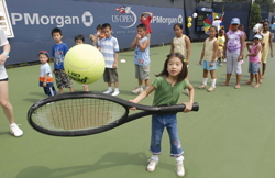 Arthur Ashe Kids' Day; little girl playing tennis; overized tennis racket