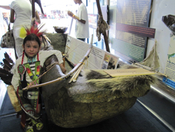 A young dance competitor poses next to an exhibit of a dug-out canoe aboard the EnviroMedia Mobile