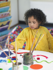 child in art class; young girl painting, arts and crafts; after-school activities