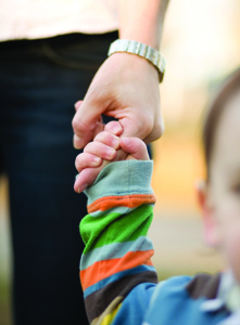 child holding nanny's hand; small child holding caregiver's, parent's hand