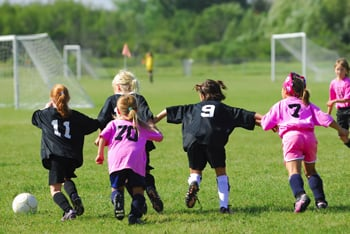 girls playing soccer; young girls on playing field; girls in pink uniforms
