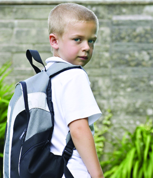 back to school anxiety; worried boy carrying a backpack, on his first day of school