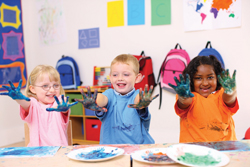 kids getting messy with paint; children finger painting in preschool classroom