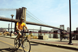 bicycle rider in front of Brooklyn Bridge; man riding a bike in Brooklyn