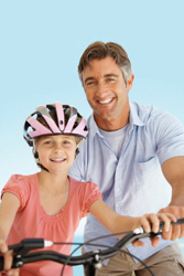 father teaching daughter how to ride a bike; dad and daughter biking, riding bikes