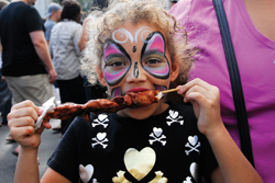 36th Annual Atlantic Antic; young girl with face painted at a fair; girl eating a kebab