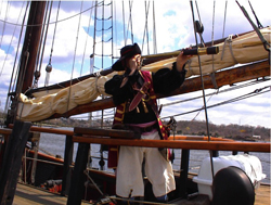 Norwalk Seaport Association's annual Oyster Festival; colonial sailor on a wooden ship with telescope; pirate