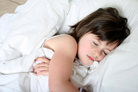 children's sleep disorders; young girl sleeping in big white bed