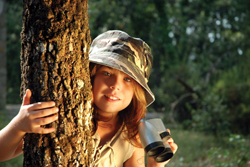 Survive: An Alternate Reality Game; little girl in camoflauge in woods, holding binoculars