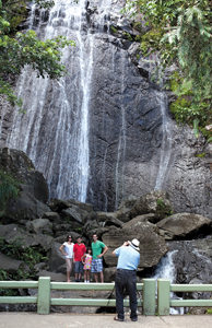 family poses at a waterfall for a photo in San Juan, Puerto Rico