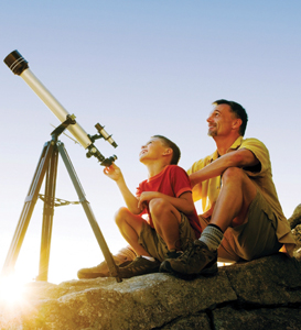 national astronomy day; father and son looking through a telescope