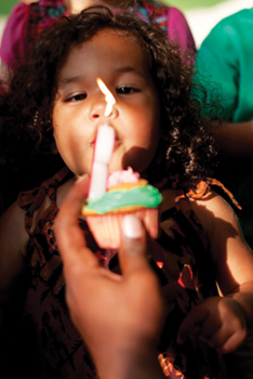 little girl blowing out the candle on her birthday cupcake