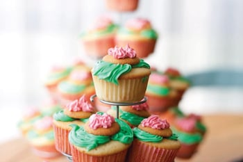 vanilla cupcakes with green and pink frosting, topped with vanilla wafers