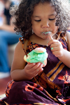 little girl eating a cupcake; young girl covered in frosting, eating cake