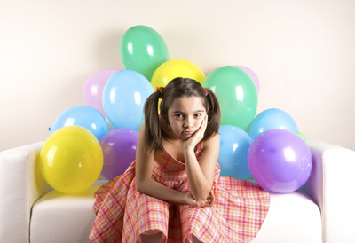 birthday girl looking sad at her party; sad young girl at a birthday party
