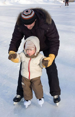 dad teaching his son how to ice skate; father and son skating on a pond in winter