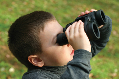 little boy looking through binoculars; child holding binoculars