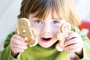 little girl holding gingerbread cookies