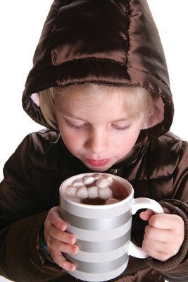 little girl holding a mug of hot chocolate with marshmallows