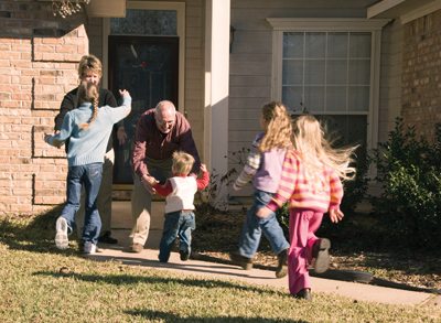 kids running to greet grandparents; grandparents greeting grandchildren; family visit