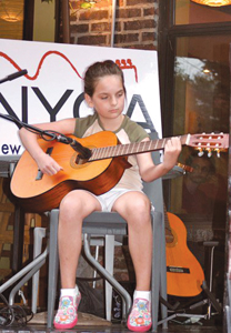 New York Guitar Academy; young girl playing an acoustic guitar