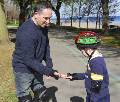 dad gives son a high five while rollerblading in the park