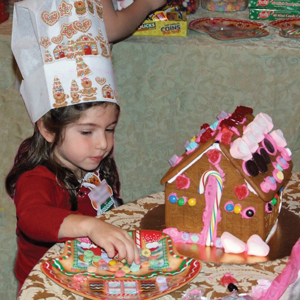 little girl decorating a gingerbread house for the holidays