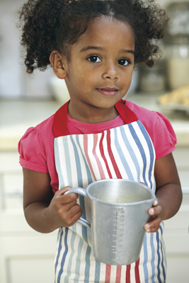 little girl baking, in the kitchen, wearing apron, holding measuring cup